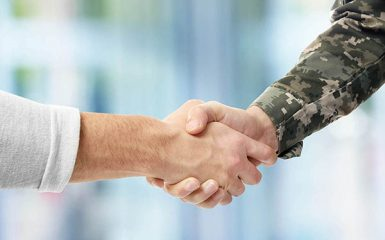 Soldier and civilian shaking hands on blurred background